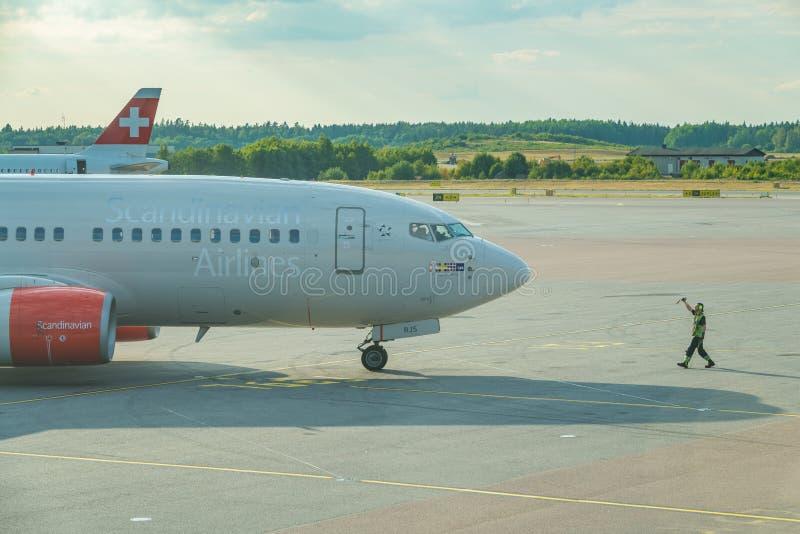 Um grupo à terra está mostrando o sinal APROVADO ao piloto escandinavo das linhas aéreas imagens de stock royalty free