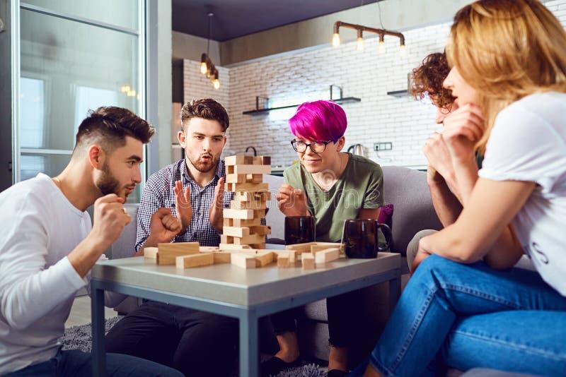 Um grupo alegre de jogos de mesa do jogo dos amigos fotografia de stock