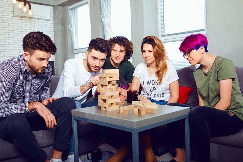 Um grupo alegre de jogos de mesa do jogo dos amigos imagem de stock royalty free