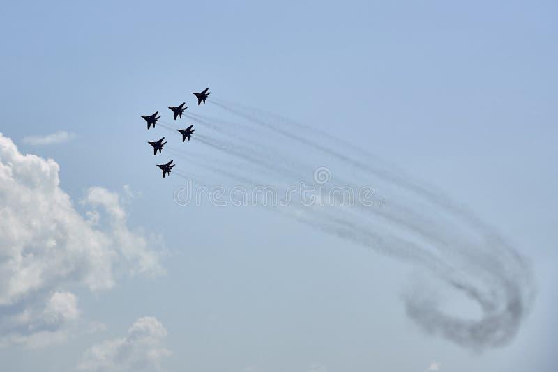 Um grupo da aviação de seis aviões MiG-29 demonstra uma forma da pirâmide contra um céu azul limpo fotografia de stock