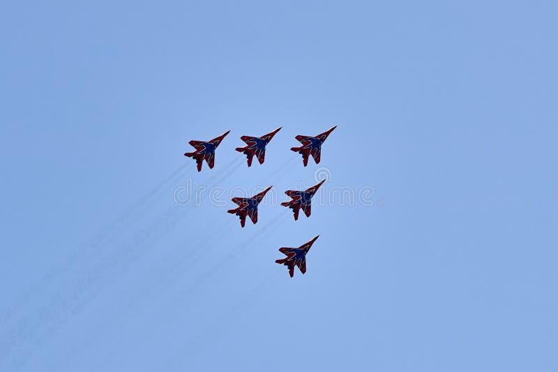 Um grupo da aviação de seis aviões MiG-29 demonstra uma forma da pirâmide contra um céu azul limpo fotos de stock royalty free