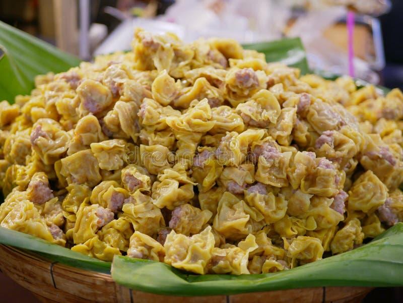Um grupo da carne de porco fluiu bolinhas de massa em uma folha do bannana em uma bandeja de bambu para a venda - Kanom tailandê fotos de stock
