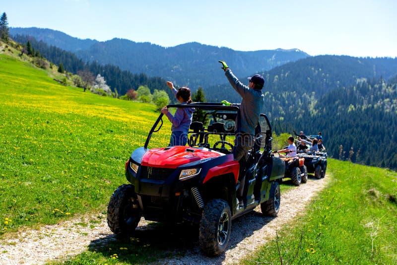 Um grupo da excursão viaja em ATVs e em UTVs nas montanhas fotografia de stock