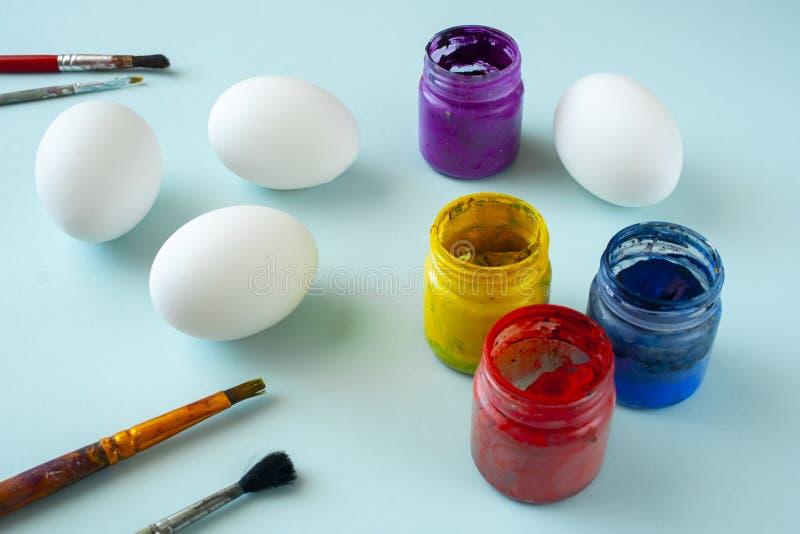 Um grupo das pinturas limpas brancas dos ovos, as azuis, as amarelas e as vermelhas e das escovas no fundo brilhante fotos de stock royalty free