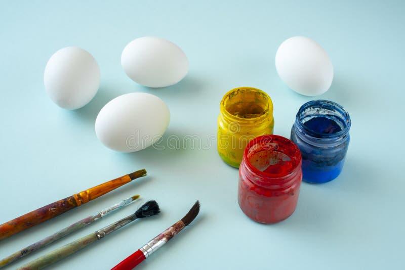Um grupo das pinturas limpas brancas dos ovos, as azuis, as amarelas e as vermelhas e das escovas no fundo brilhante imagem de stock