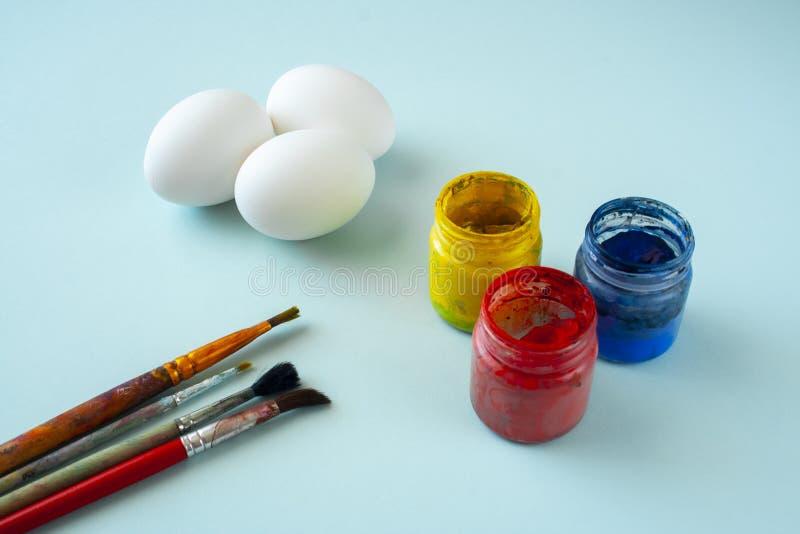 Um grupo das pinturas limpas brancas dos ovos, as azuis, as amarelas e as vermelhas e das escovas no fundo brilhante fotos de stock