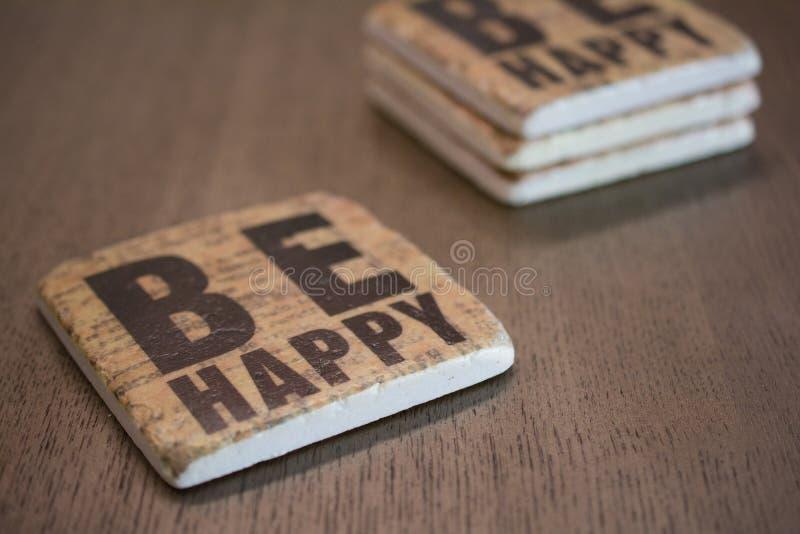 Um grupo das pousas-copos de pedra empilhadas em uma leitura de madeira da superfície da tabela esteja feliz fotos de stock royalty free