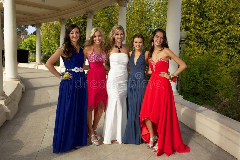 Um grupo de adolescentes que levantam em seu baile de finalistas veste-se fotos de stock