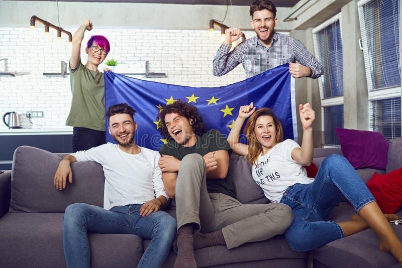 Um grupo de amigos com uma bandeira europeia em um partido fotos de stock