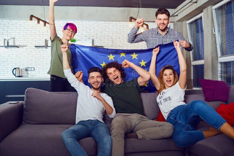 Um grupo de amigos com uma bandeira europeia em um partido imagem de stock royalty free
