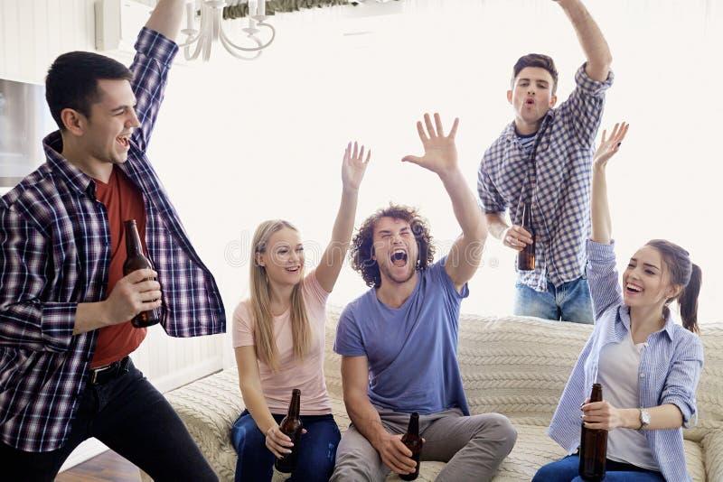Um grupo de amigos do partido em um aumento alegremente suas mãos acima fotografia de stock