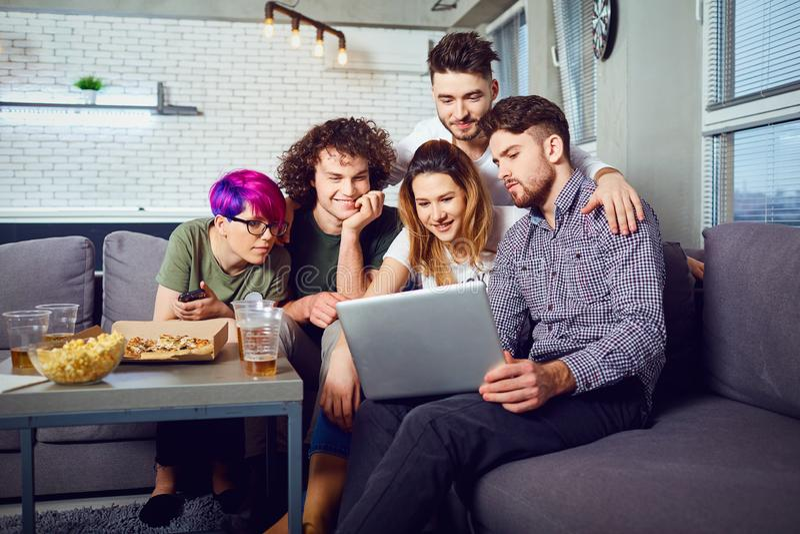 Um grupo de amigos dos estudantes no lazer com um portátil em um roo fotografia de stock