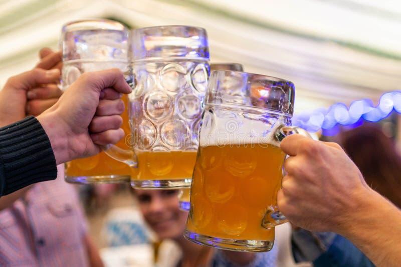 Um grupo de amigos dos jovens que brindam com vidros da cerveja no foco macio de Oktoberfest Alemanha DOF raso foto de stock