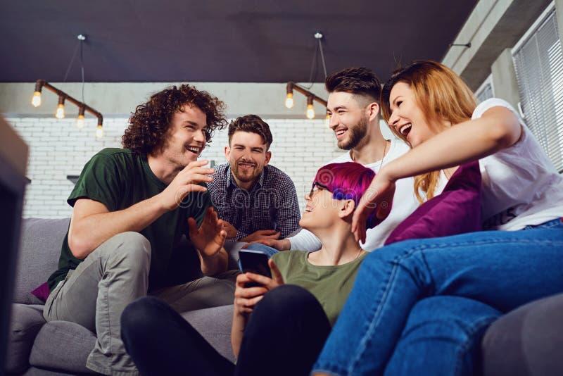 Um grupo de amigos em uma reuni?o que falam junto na sala fotos de stock royalty free