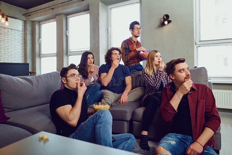 Um grupo de amigos está tendo o divertimento que olham a tevê na sala foto de stock royalty free