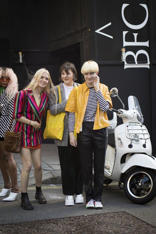Um grupo de amigos fashionably vestidos que conversam na entrada à construção imagem de stock royalty free