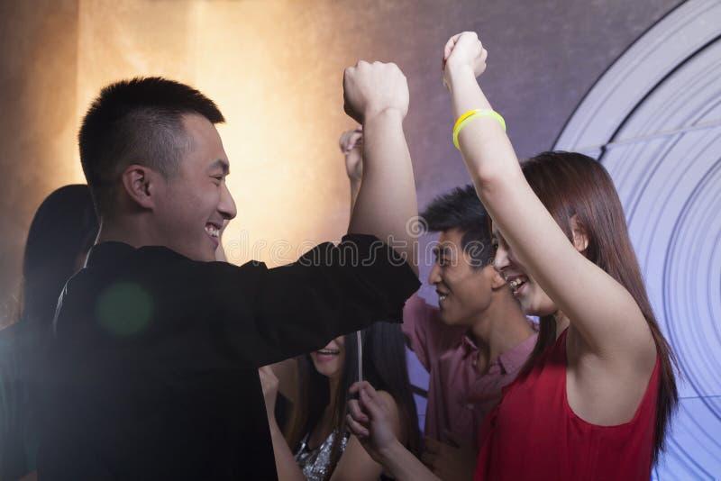 Um grupo de amigos novos que dançam em um clube noturno fotos de stock