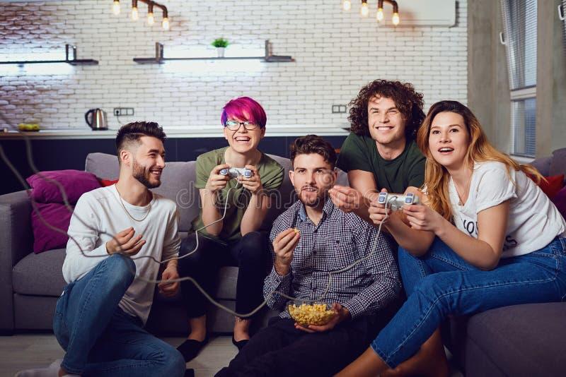Um grupo de amigos que jogam jogos de vídeo na sala imagens de stock