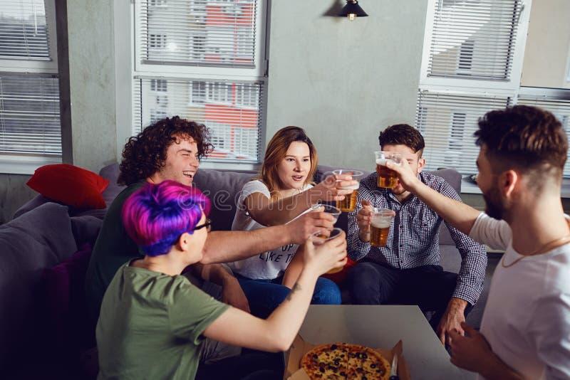 Um grupo de amigos ? vidros do tinido com cerveja na sala imagem de stock royalty free