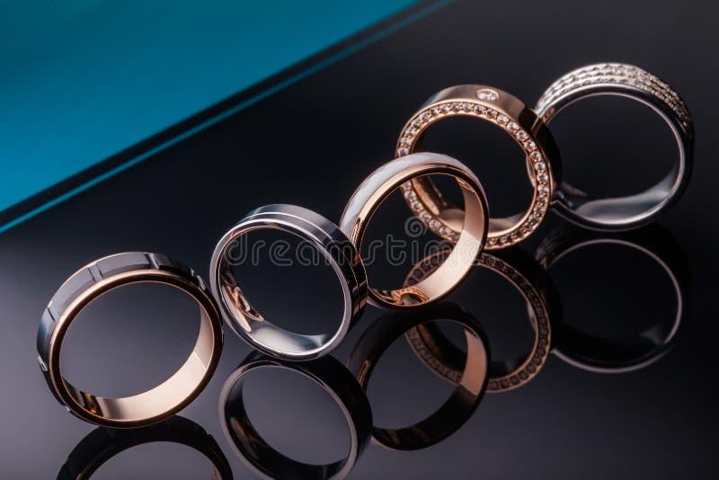 Um grupo de aneis de noivado bonitos com diamantes em uma obscuridade elegante - fundo azul com reflexão Close up, ouro, prata, p imagens de stock royalty free
