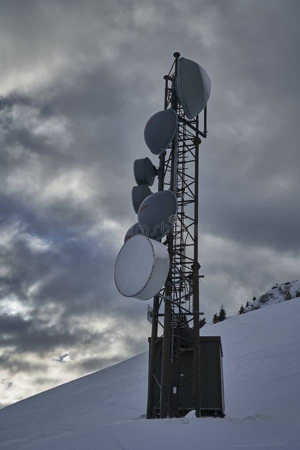 Um grupo de antenas da telecomunicação em uma torre fotos de stock