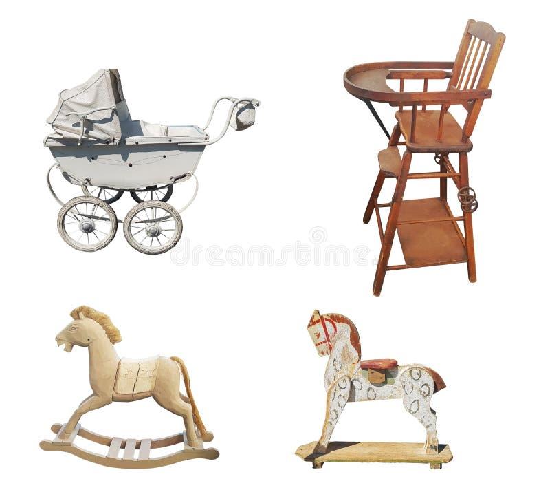 Um grupo de artigos do vintage das crianças idosas: um carrinho de criança, um cadeirão, um cavalo de madeira no fundo branco fotografia de stock