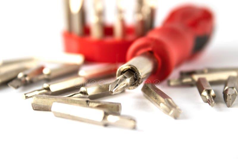 Um grupo de bocados para chaves de fenda em um fundo branco foto de stock