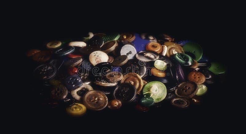 Um grupo de botões velhos no fundo preto ilustração stock