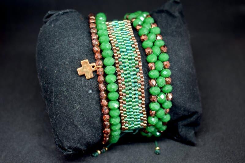 Um grupo de braceletes frisados em uma superfície escura cores do verde e do ouro imagens de stock