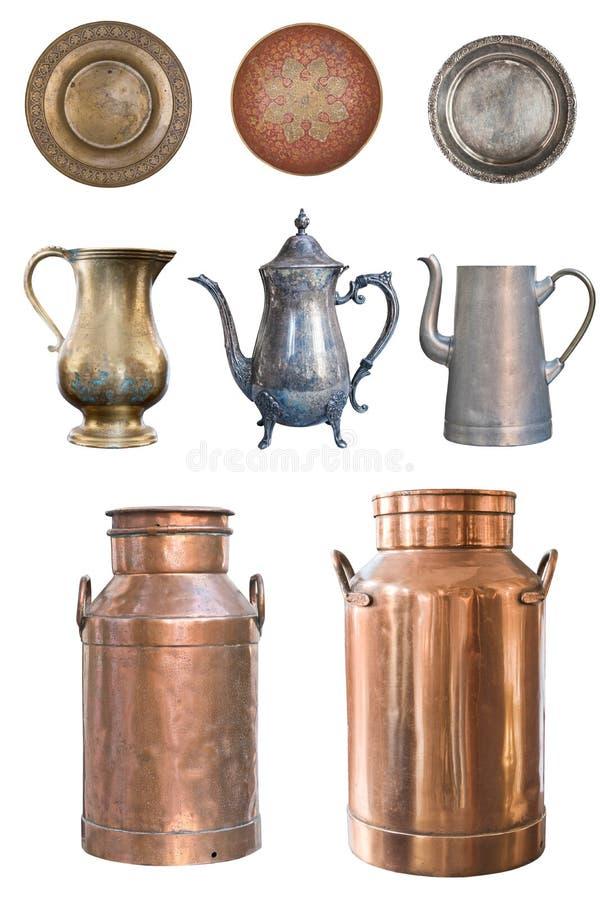 Um grupo de bules velhos bonitos, dos leiteiros de cobre e das placas isolados em um fundo branco fotografia de stock