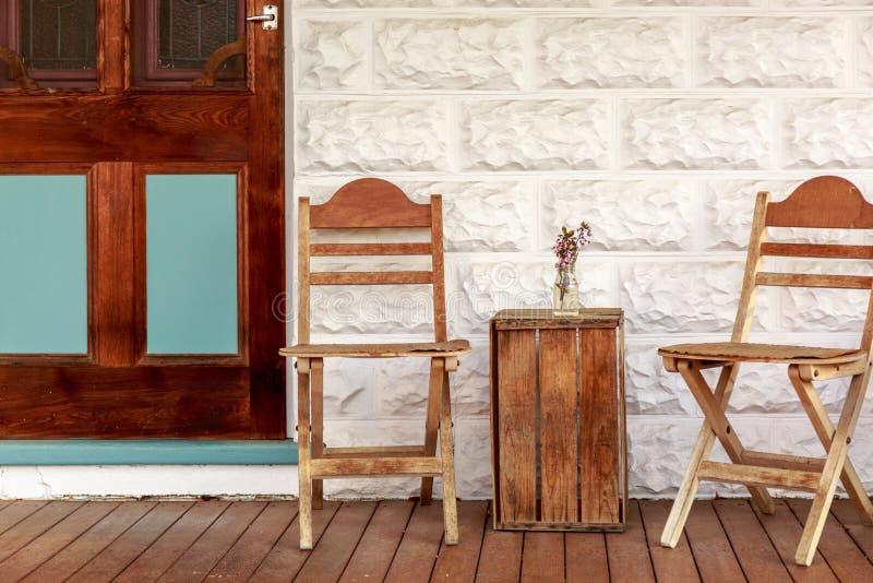 Um grupo de cadeira e de tabela de madeira do vintage contra a parede branca foto de stock royalty free