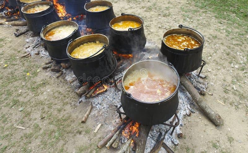 Um grupo de caldeirões e de chaleira no fogo no acampamento do turista imagens de stock