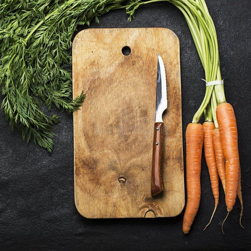 Um grupo de cenouras suculentas frescas com partes superiores em um fundo escuro com uma placa de corte do vintage e uma faca par fotos de stock royalty free