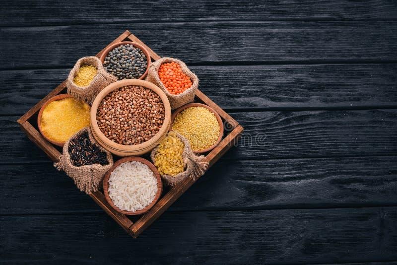 Um grupo de cereais e de grões em uma cesta de madeira em um fundo de madeira foto de stock royalty free