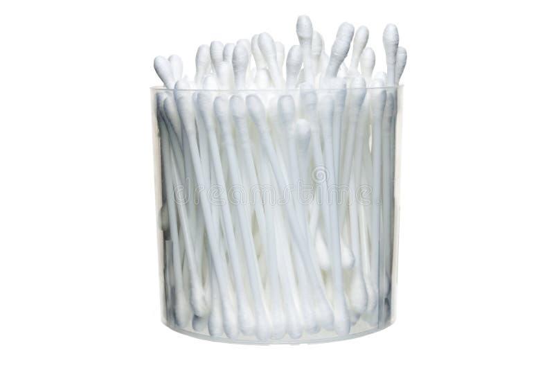 Um grupo de cotonetes de algodão em um recipiente plástico em um fundo branco isolate imagem de stock