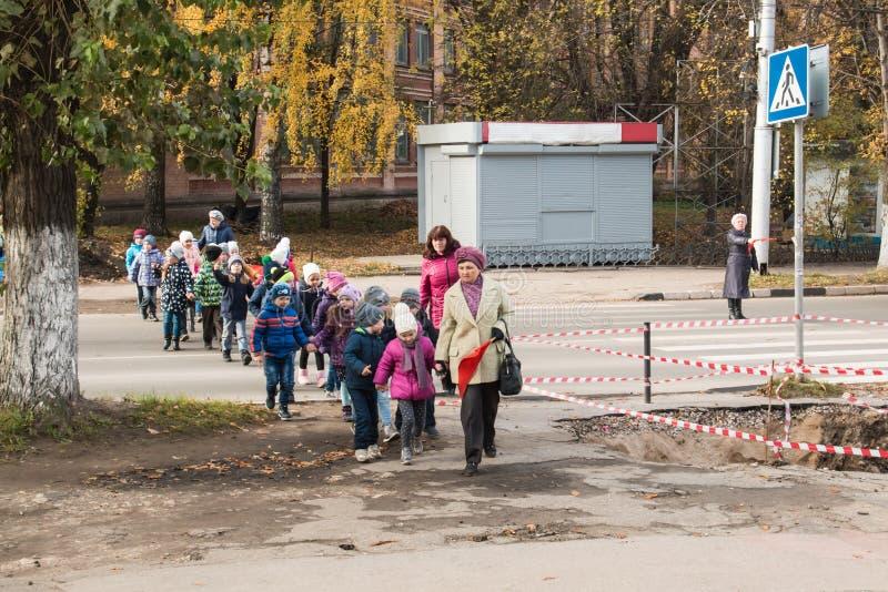 Um grupo de crianças cruza o caminho de acordo com as regras da estrada imagens de stock royalty free
