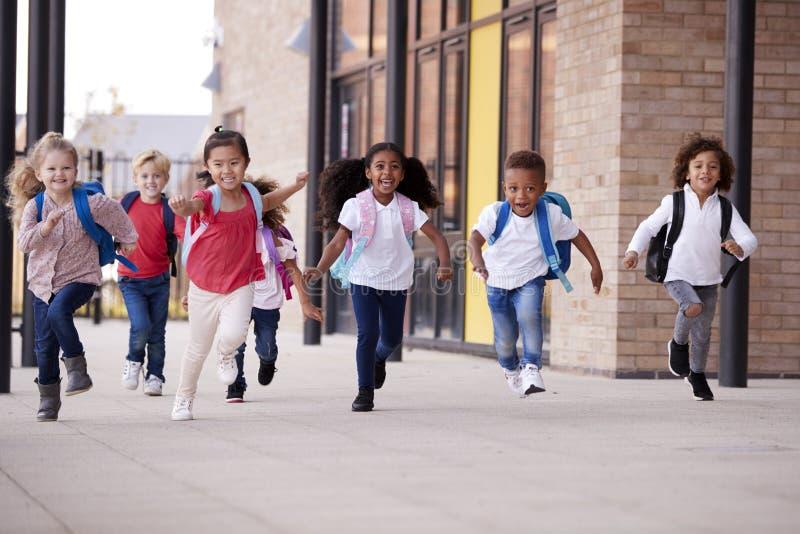 Um grupo de crianças multi-étnicas de sorriso da escola que correm em uma passagem fora de seu prédio da escola infantil após uma fotos de stock