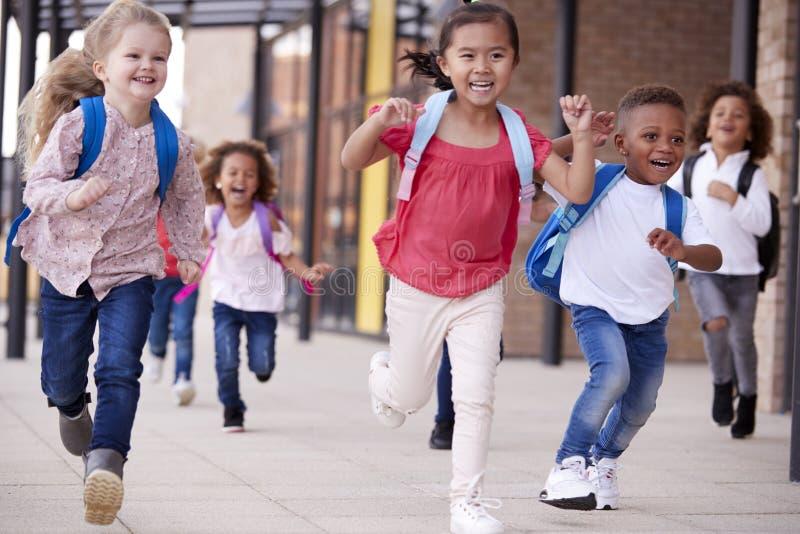 Um grupo de crianças multi-étnicas de sorriso da escola que correm em uma passagem fora de seu prédio da escola infantil após uma fotografia de stock