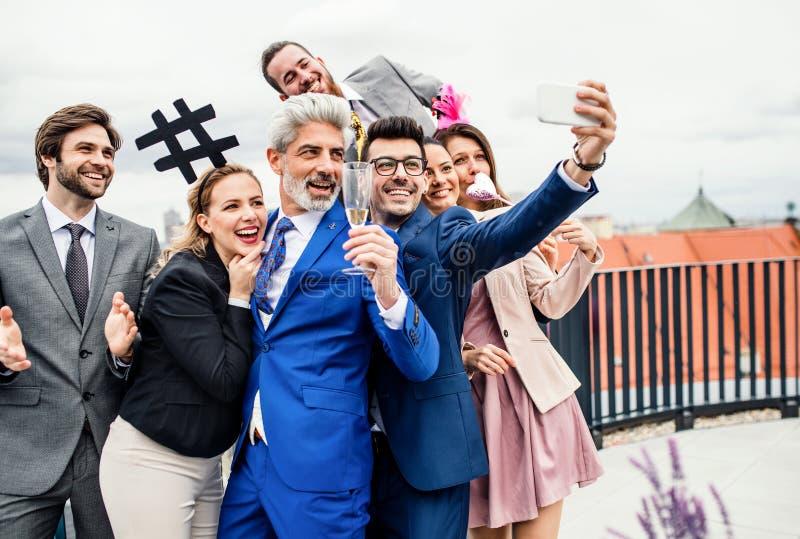 Um grupo de empresários alegres fora no terraço do telhado na cidade, tomando o selfie no partido fotografia de stock