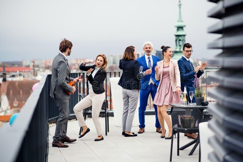 Um grupo de empresários alegres que têm um ar livre do partido no terraço do telhado na cidade foto de stock royalty free
