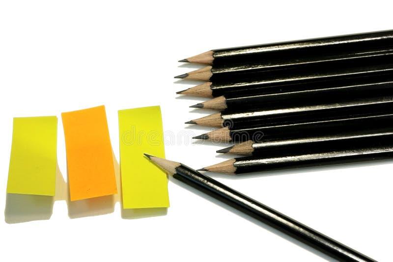 Um grupo de esboçar lápis e três notas pegajosas em amarelo e em alaranjado foto de stock