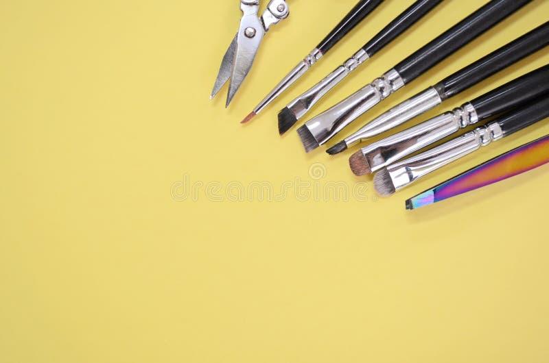 Um grupo de escovas diferentes do maquilhador e as tesouras encontram-se em um canto com copyspace para o texto na cor amarela imagens de stock