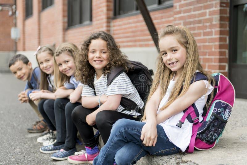 Um grupo de estudantes fora na escola que está junto imagem de stock