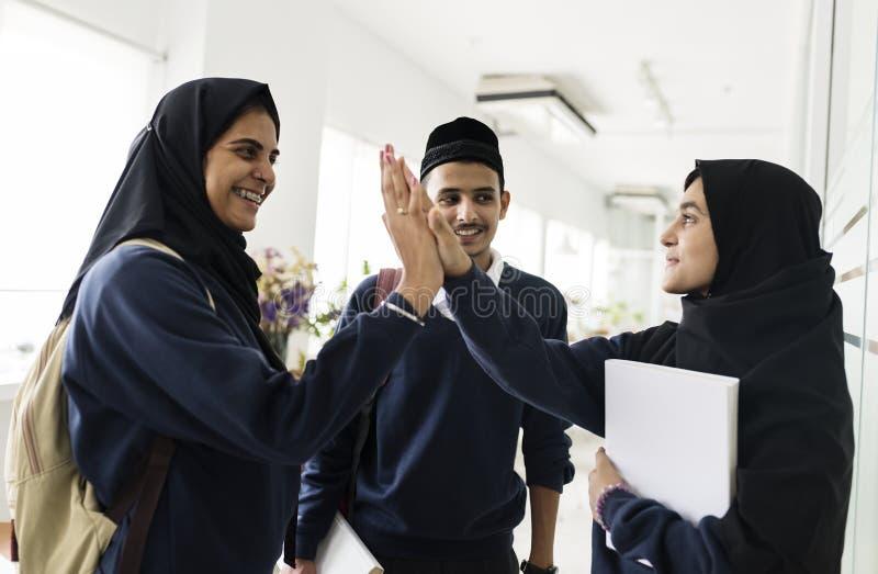 Um grupo de estudantes muçulmanos que fazem hi-5 foto de stock royalty free