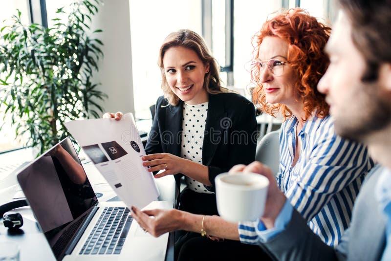 Um grupo de executivos novos com o port?til que senta-se em um escrit?rio, falando fotos de stock royalty free