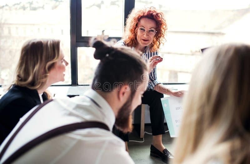 Um grupo de executivos novos que sentam-se no assoalho em um escrit?rio, falando fotografia de stock
