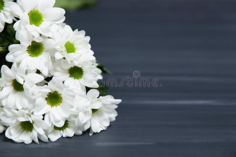 Um grupo de flores da margarida branca na superfície rústica da tabela do quadro, com fundo do espaço da cópia do borrão fotografia de stock