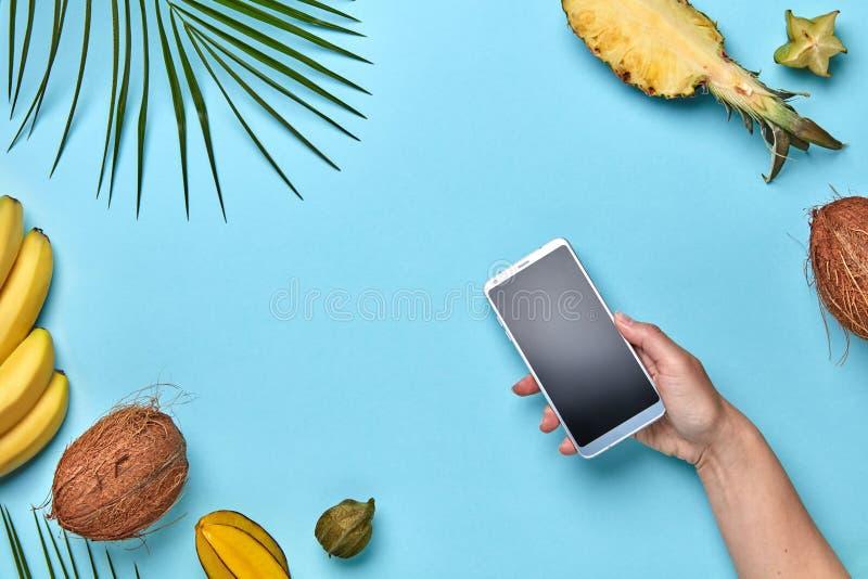 Um grupo de frutos exóticos diferentes e de uma folha de palmeira Uma mão do ` s da mulher está guardando um telefone celular em  imagem de stock