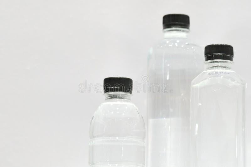 Um grupo de garrafas pl?sticas no fundo branco da parede imagem de stock