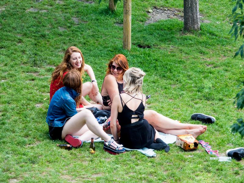 Um grupo de jovens mulheres bonitas aprecia o sol na grama de um parque público foto de stock royalty free